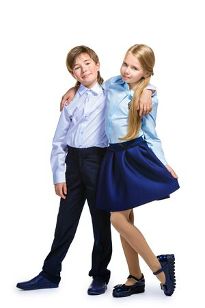 School fashion. Two cute children in school uniform posing at studio. Isolated over white background. Copy space. Full length portrait. Banque d'images