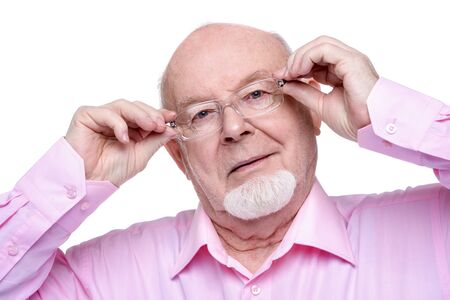 Close-up portrait of an elderly man wearing glasses and a pink shirt. Older generation.