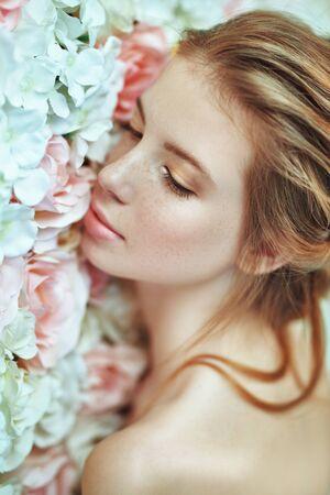 Frühlingsmädchen. Porträt einer schönen jungen Frau mit frischer, klarer Haut und schönen Sommersprossen auf einem Hintergrund zart blühender Rosen. Schönheitskonzept.