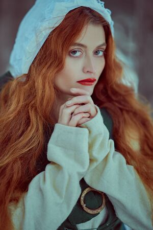 Portrait of a beautiful young woman with long red hair wearing medieval clothes. Historical reconstruction of the Middle Ages. 版權商用圖片