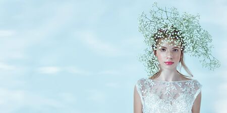 Beautiful young girl with lovely freckles on her face and in a gypsophila wreath on a white background. Inspiration of spring and summer. Perfume, cosmetics concept. Copy space.