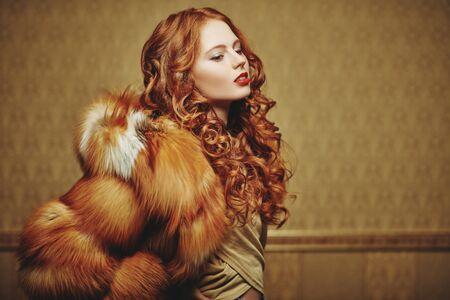 Estilo de abrigo de piel. Retrato de una bella mujer sensual con el pelo rojo en un lujoso abrigo de piel de zorro. Moda de belleza de invierno.