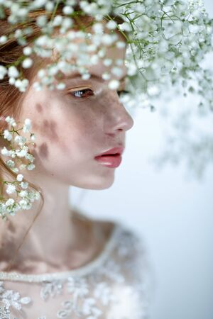 Beautiful young girl with lovely freckles on her face and in a gypsophila wreath on a white background. Inspiration of spring and summer. Perfume, cosmetics concept. Stock Photo
