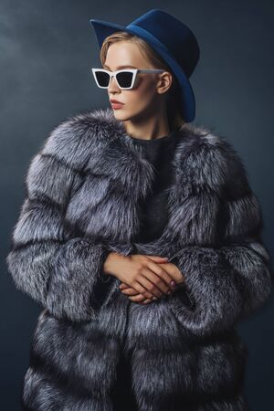 A portrait of a young fashionable woman in a hood and sunglasses. Beauty, optics, fashion.