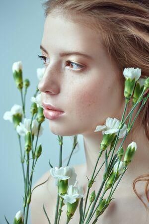 Schönheitsporträt eines zarten jungen Mädchens, das mit weißen Nelkenblumen auf einem weißen Hintergrund aufwirft. Parfüm, Schönheitskosmetikkonzept.