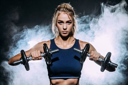 Muscular young woman with beautiful athletic body doing exercises with dumbbells. Fitness, bodybuilding. Health care.