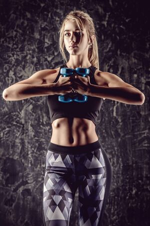Muscular young woman with beautiful athletic body doing exercises with dumbbell. Fitness, bodybuilding. Health care. 스톡 콘텐츠