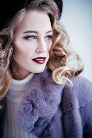A close up portrait of a beautiful woman wearing a fur coat and a hat. Beauty, winter fashion, style. Banco de Imagens