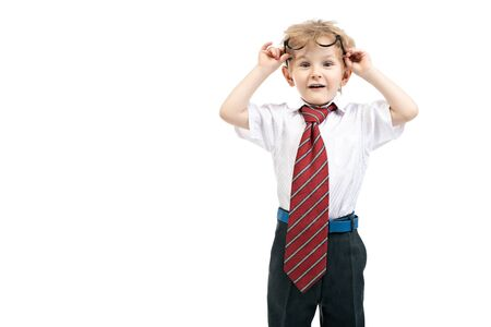 A portrait of a funny young schoolboy posing in the studio over the white background. Kids fashion for school, education.