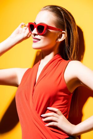 A portrait of a cheerful young lady posing in sunglasses over the yellow background. Summer, beauty.