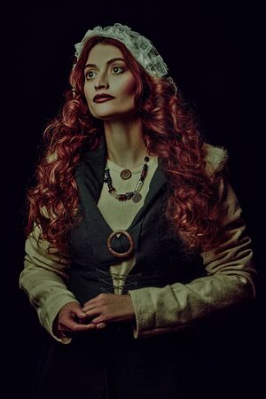 Portrait of a beautiful young woman with long red hair wearing medieval clothes on a dark background. Historical reconstruction of the Middle Ages. Stock Photo