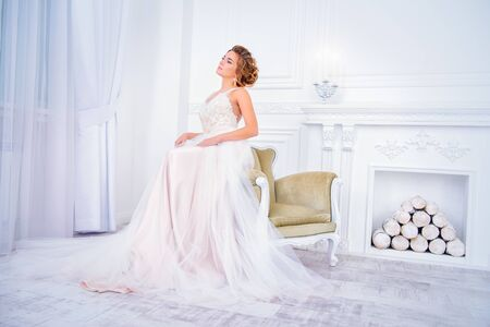 Full length portrait of a beautiful bride woman in elegant pale apricot wedding dress. Luxurious apartments.