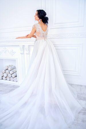 Pełnej długości portret pięknej kobiety panny młodej w eleganckiej sukni ślubnej blady morelowy. Luksusowe apartamenty. Zdjęcie Seryjne