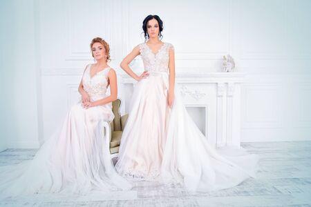 Zwei exquisite schöne Bräute in eleganten Brautkleidern stehen in weißen Luxusappartements. Hochzeitsmode.