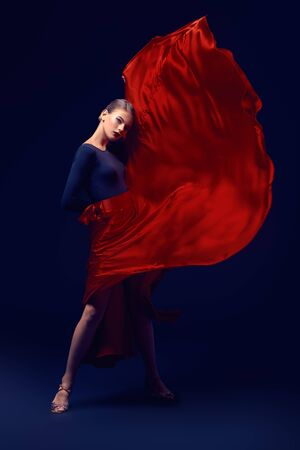 Beautiful girl professional dancer performs latino dance. Passion and expression. Black background. Stock Photo