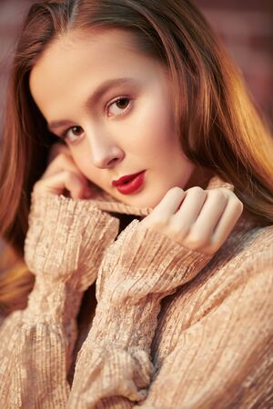 Charming young girl with natural make-up and in a light beige dress smiles slightly. Beauty and cosmetics concept. Lifestyle. Reklamní fotografie