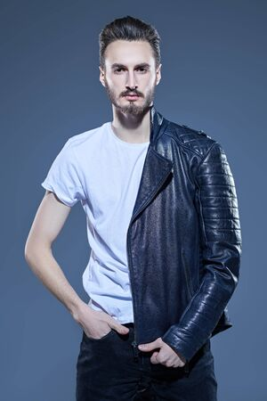 Mens fashion. Handsome man in casual white t-shirt and black leather jacket. Studio portrait.