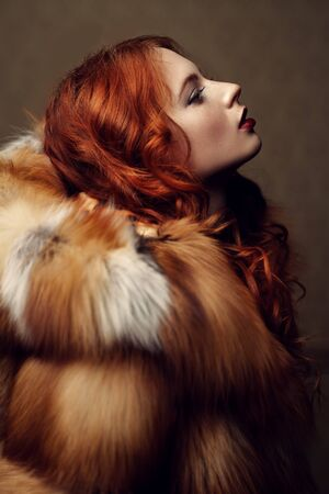 Fur coat style. Portrait of a beautiful sensual woman with red hair in a luxurious fox fur coat. Winter beauty fashion.