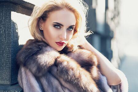Ein Porträt einer schönen blonden Dame, die auf die Straße geht. Schönheit, urbane Mode, Stil.