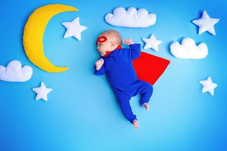 Little baby superhero with red cape flies through the night sky. Reklamní fotografie