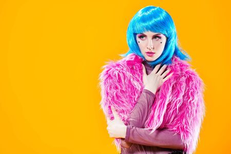 Portrait of an attractive party girl with bright pink makeup and blue wig wearing pink fur coat on a yellow background. Make-up and cosmetics, hairstyle. Fashion girl. Copy space.