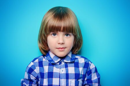 ?ute six-year-old boy poses in checkered shirt over blue background. Children's fashion and beauty. Studio shot.