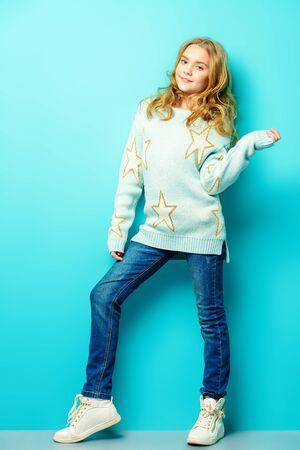 Pretty nine year old girl poses over blue background. and smiling. Kid's fashion. Spring style.