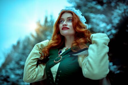 Portrait of a beautiful young woman with long red hair wearing medieval clothes walks through a winter snowy forest. Historical reconstruction of the early Middle Ages. Christmas tale. Stock Photo
