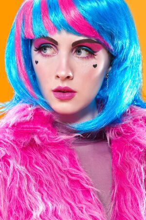 Portrait of an attractive party girl with bright pink makeup and blue wig wearing pink fur coat on a yellow background. Make-up and cosmetics, hairstyle. Fashion girl.