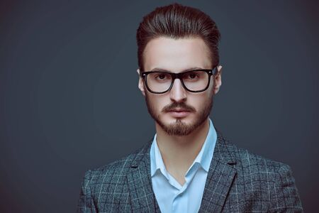 Elegant handsome man in spectacles and fashionable suit. Business style. Studio portrait. Copy space.