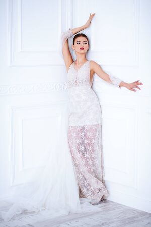 A full length portrait of a charming lady in a wedding dress posing indoor. Wedding fashion, bride.
