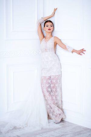 Een portret van volledige lengte van een charmante dame in een trouwjurk die binnenshuis poseert. Huwelijksmode, bruid.