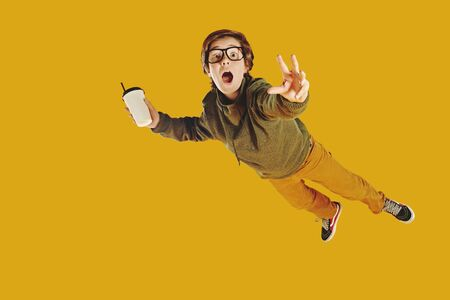 Emotional boy teenager in glasses flies with a glass of coffee and screams in surprise. Yellow background. Copy space.