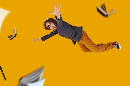 Educational concept. Emotional boy teenager student flies through the air surrounded by books. Yellow background. Standard-Bild