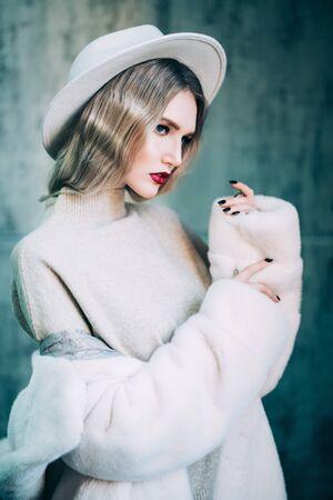 A portrait of a thoughtful beautiful girl wearing a white fur coat. Beauty, winter fashion.