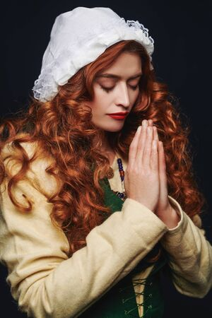 Close up portrait of a prayer beautiful young woman with long red hair wearing medieval clothes on a dark background. Historical reconstruction of the Middle Ages.