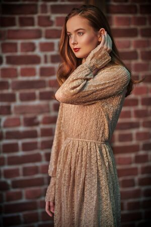 Pretty young girl with natural make-up and in a light beige dress looks out the window and smiles slightly. Brick wall background. Beauty, Fashion concept.