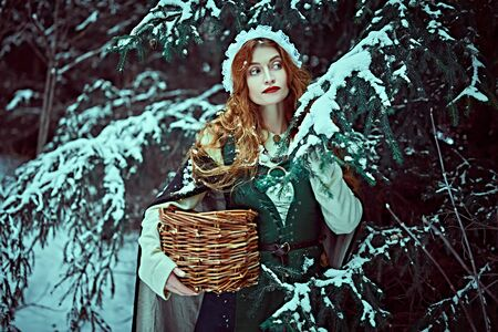 Portrait of a beautiful young woman with long red hair wearing medieval clothes walks through a winter snowy forest. Historical reconstruction of the early Middle Ages. Christmas tale. 写真素材