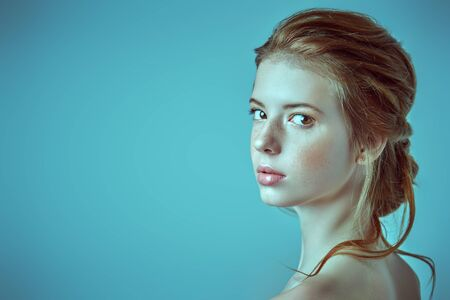 Beauty woman. Portrait of a beautiful young girl with fresh clear skin on a soft blue background. Copy space.