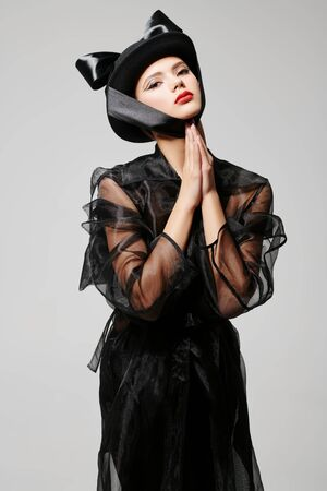 Hats fashion. Portrait of a charming young woman in a fashionable hat on a gray background. Makeup and cosmetics. 스톡 콘텐츠