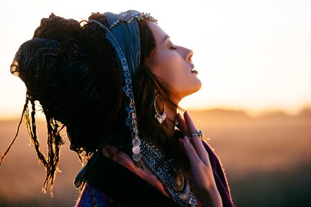Beautiful fashion model posing in boho style clothes in the rays of the sunset. Outdoor fashion.