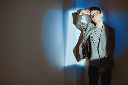 Men's beauty, fashion. Handsome young man in classic suit and spectacles posing at studio by the white wall in blue light.