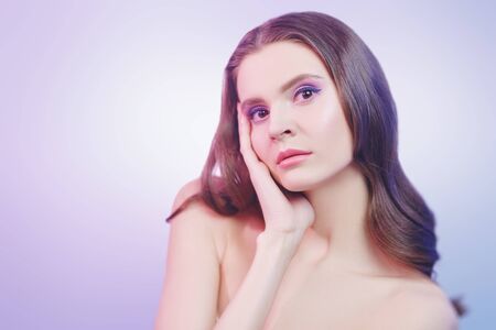 Portrait of a beautiful young woman with gentle makeup on a lilac background. Beauty, skincare, cosmetics concept. Healthcare. Stockfoto
