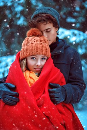 Couple of happy romantic young people hugging in a winter park and smiling. Winter season.