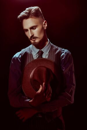 Courageous handsome man in elegant classical suit and a hat stands in the dark, lit by a ray of light. Retro style. Luxury. Criminal world, mafia.
