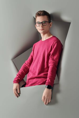 Beauty, fashion concept. Modern young man in casual clothes and glasses posing at studio with grey background.