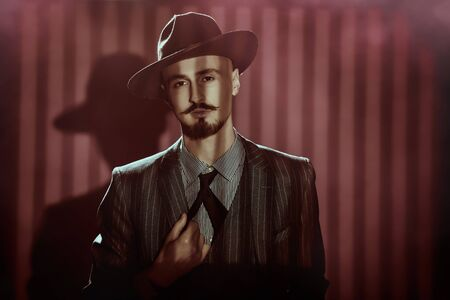 Portrait of a handsome man in elegant classical suit and a hat standing in a dark room lit by streaks of light. Retro style. Luxury. Men's beauty, fashion. Archivio Fotografico