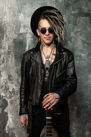 A portrait of a stylish punk man against the background of grunge. Modern men fashion. Foto de archivo
