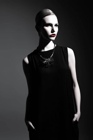 A portrait of a confident lady wearing a black dress and posing in the studio over the grey background. Beauty, make-up, style.