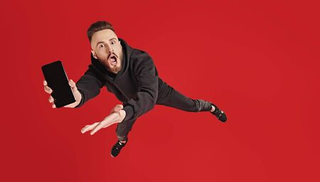 Excited young man flies through the air with his smartphone and shows on his screen. New trendy technologies in smartphones. Studio shot on a red background. Copy space.